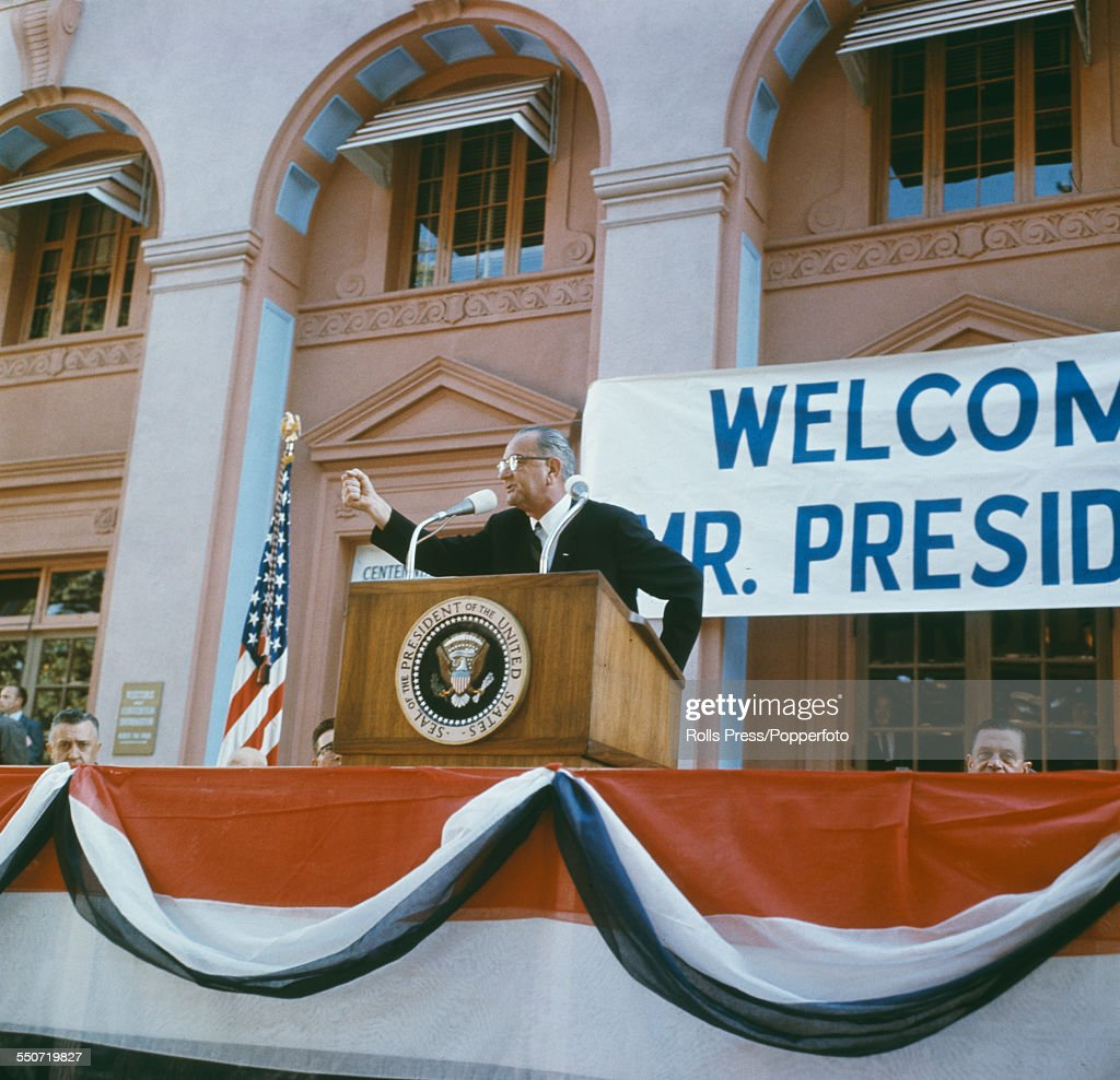 President of the United States Lyndon B Johnson pictured standing on a podium to address supporters and crowds on the 1964 presidential election...