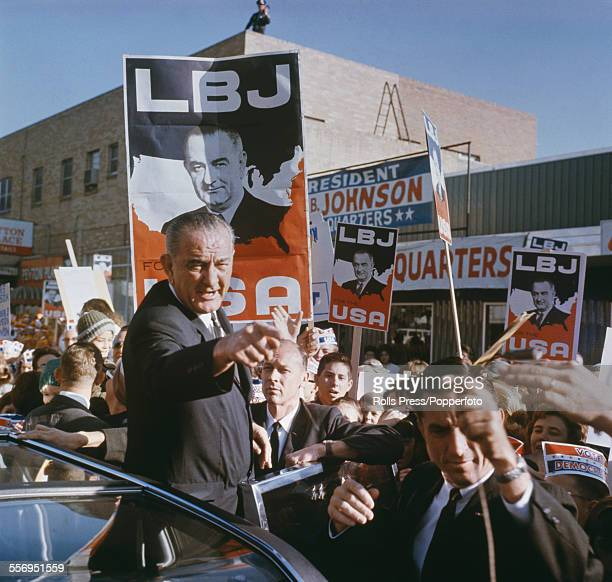 President of the United States Lyndon B Johnson pictured waving to supporters and crowds of spectators from the door of a limousine during the 1964...