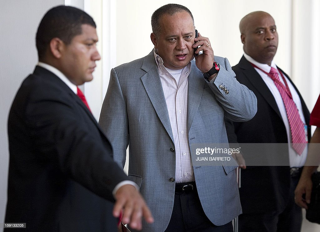 President of the Venezuelan National Assembly, Diosdado Cabello (C), speaks on the phone before a session in Caracas on January 8, 2013. Cabello announced today that due to health reasons, Venezuelan President Hugo Chavez will not be able to take the oath to be sworn in for a fourth term in office next January 10. AFP PHOTO/JUAN BARRETO