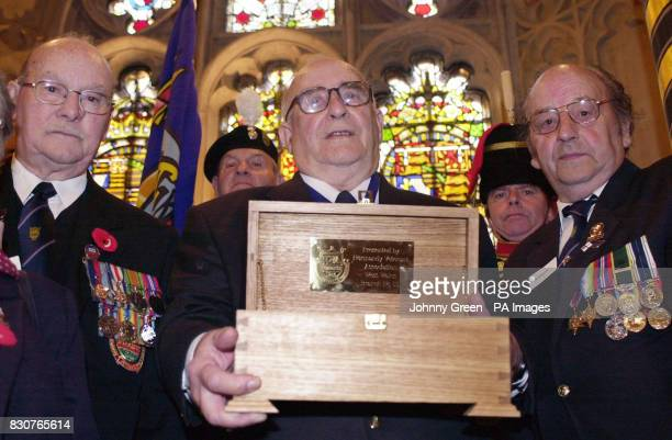 President of the West Wales Branch of the Normandy Veterans Association Doug Gausden holds a casket made from cherry wood and filled with sand from...