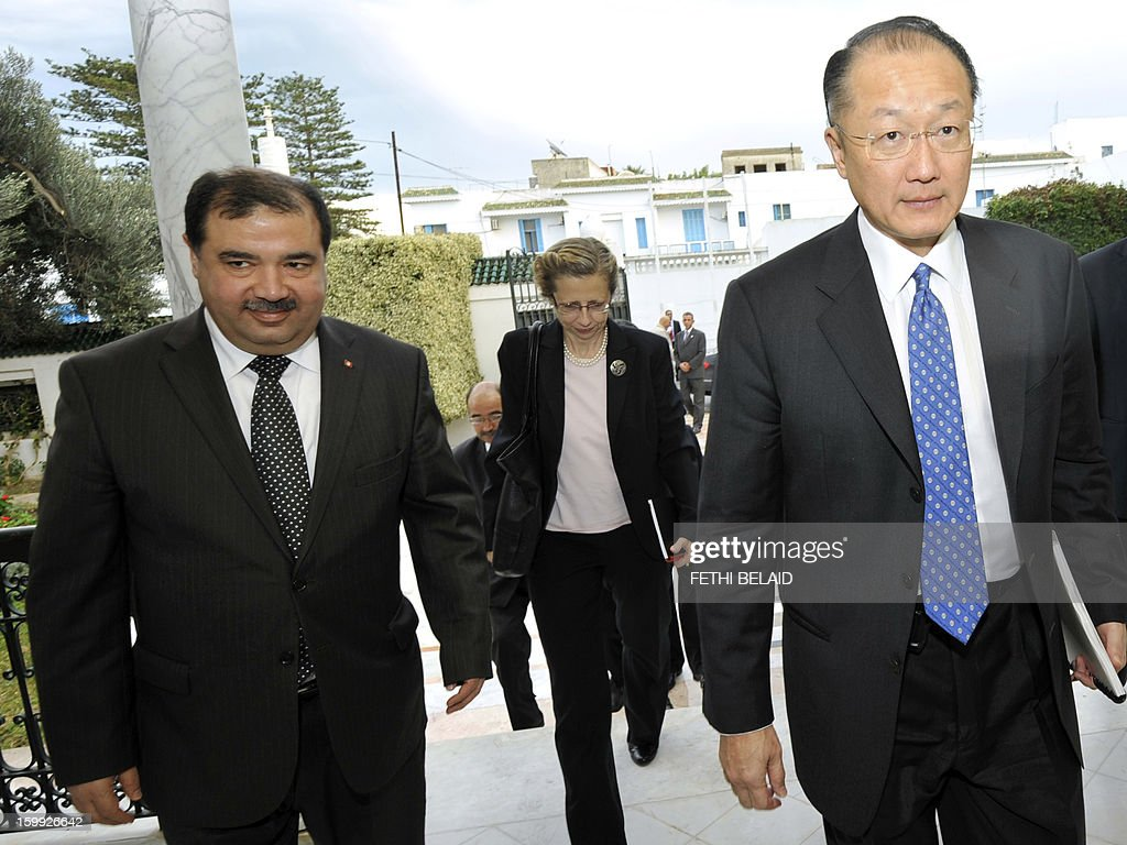 President of the World Bank Jim Yong Kim (R) arrives for a meeting with Tunisian Investisment and International Cooperation Minister Riadh Bettaieb (L) on January 23, 2013 in Tunis. Kim is on 2 day official visit to Tunisia to discuss boosting economic growth. AFP PHOTO / FETHI BELAID