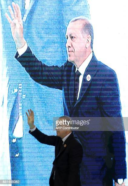 President of Turkey and Chairman of the Turkey's ruling Justice and Development Party Recep Tayyip Erdogan greets the audience next to a screen...