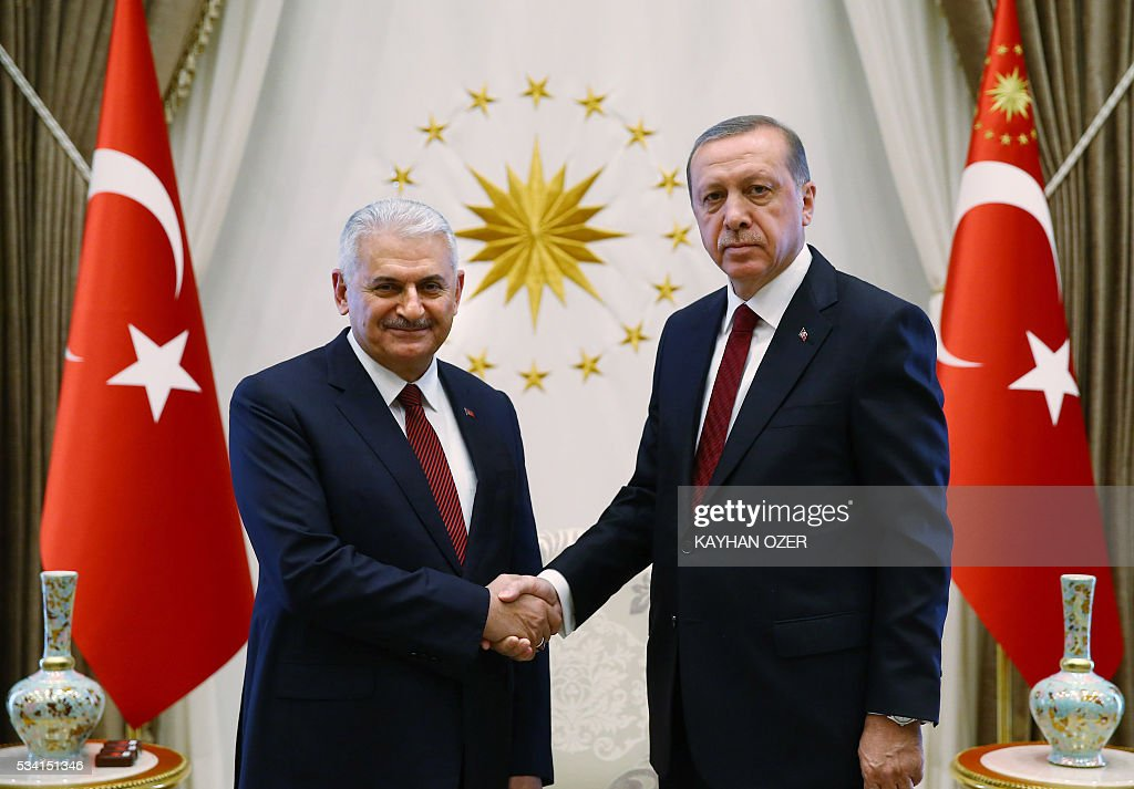 President of Turkey Recep Tayyip Erdogan (R) and Turkish Prime Minister Binali Yildirim (L) shake hands prior to the meeting of 65th Cabinet of Turkey at Presidential Complex, in Ankara, Turkey on May 25, 2016. / AFP / KAYHAN