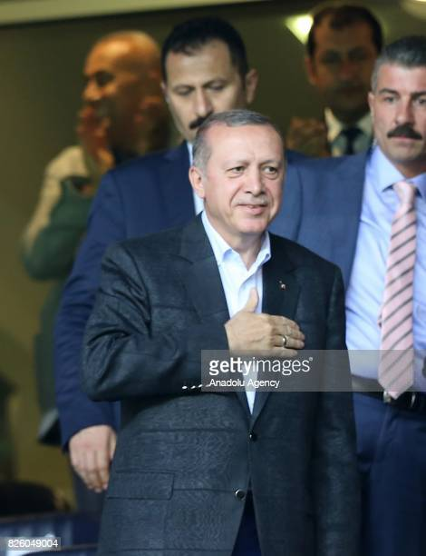 President of Turkey Recep Tayyip Erdogan salutes people as he attends the UEFA Europa League third qualifying round 2nd leg match between Fenerbahce...