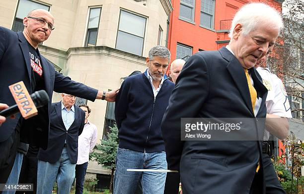 President of United to End Genocide Tom Andrews pats actor George Clooney on the back as he is arrested with his journalist father Nick Clooney and...