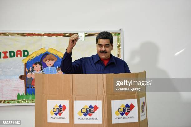 President of Venezuela Nicolas Maduro holds his vote receipt after casting his vote at a polling station during municipal election in Caracas...