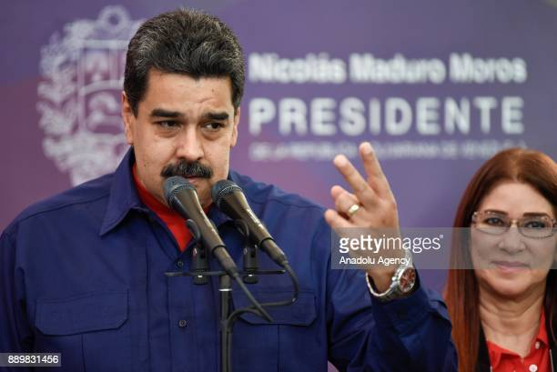 President of Venezuela Nicolas Maduro makes a speech during a press conference as he is flanked by his wife First Lady Cilia Flores after casting...