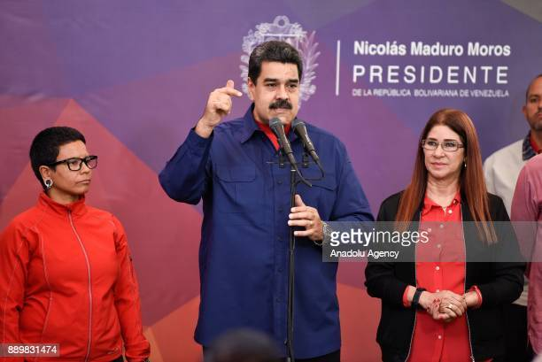 President of Venezuela Nicolas Maduro makes a speech during a press conference as he is flanked by his wife First Lady Cilia Flores and Candidate to...