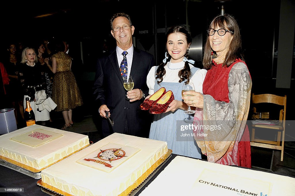 President of Western Costume Company, Eddie Marks, the model wearing the Dorthy dress and holding thr ruby red sippers that were worn by Judy Garland in 'The Wizard Of Oz' and head of research at Western Costum Company Bobi Garland prepare to cut the cake at The Costume Council Of LACMA Celebrates The Western Costume Company: The First 100 Years at the Bing Theatre At LACMA on June 20, 2012 in Los Angeles, California.