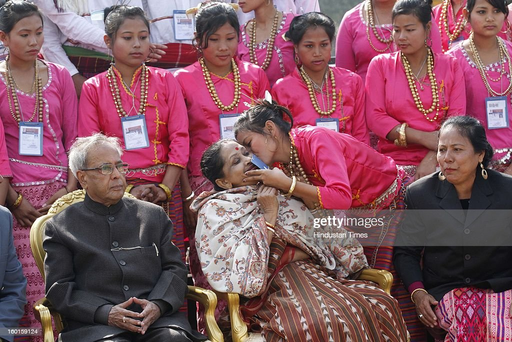 President Pranab Mukherjee looks on as an artist from Tripura kisses his wife <a gi-track='captionPersonalityLinkClicked' href=/galleries/search?phrase=Suvra+Mukherjee&family=editorial&specificpeople=10170312 ng-click='$event.stopPropagation()'>Suvra Mukherjee</a> (M) during group photo with tableau artists who participated in the Republic Day Parade-2013 at Rashtrapati Bhavan on January 27, 2013 in New Delhi, India.
