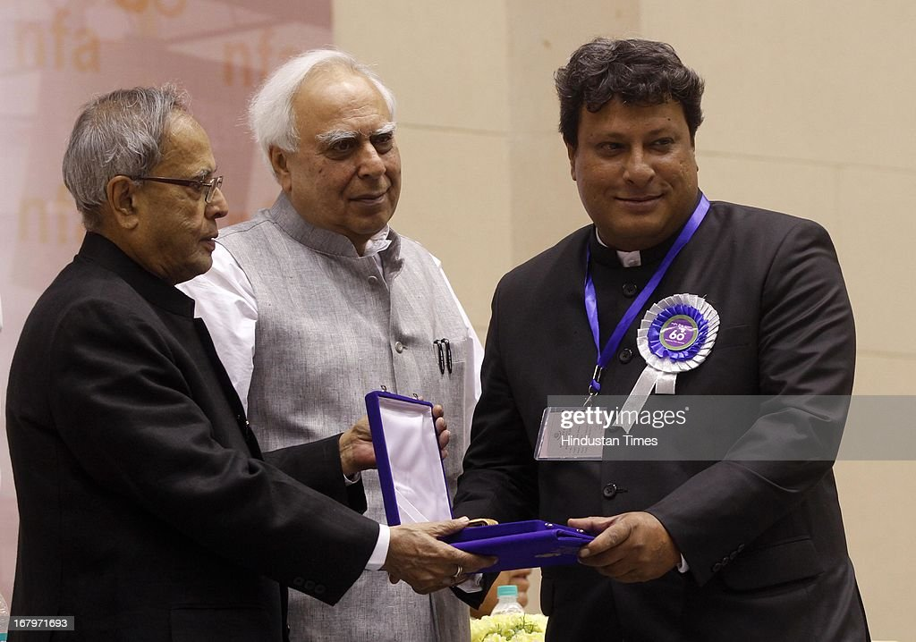 President Pranab Mukherjee presenting best director award to Tigmanshu Dhulia for his film Pan Singh Tomar at 60th National Film Awards on May 03, 2013 in New Delhi , India. Paan Singh Tomar' got best film award and its lead actor Irrfan Khan adjudged as the best actor.