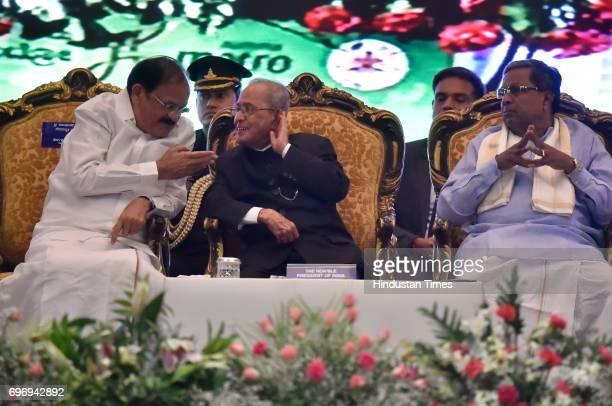 President Pranab Mukherjee speaks to Union Minister for Urban Development Venkaiah Naidu as Karnataka Chief Minister Siddaramaiah looks on during the...