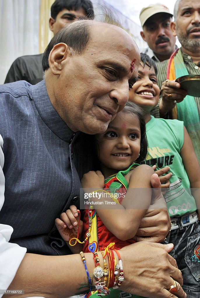 BJP President Rajnath Singh hugging young girl after she tied Rakhi on his wrist on the occasion of Rakhi festival at his house on August 21, 2013 in New Delhi, India. Raksha Bandhan, the festival of love between brothers and sisters, is being celebrated across the country today with full enthusiasm.