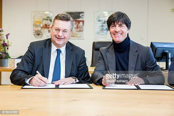 President Reinhard Grindel and Joachim Loew head coach of the German National Football team sign a contract during the announcement of the renewal of...