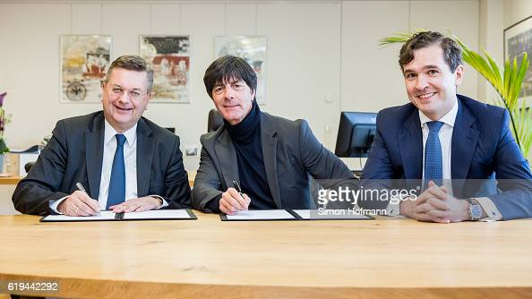 President Reinhard Grindel Joachim Loew head coach of the German National Football team and DFB General Secretary Friedrich Curtius sign a contract...