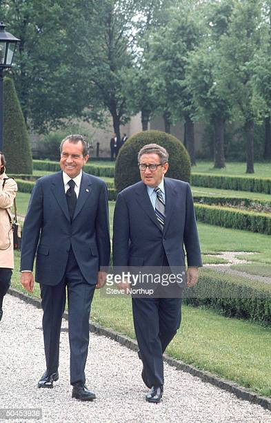 President Richard M Nixon and Secretary of State Henry Kissinger strolling through park during visit to Austria