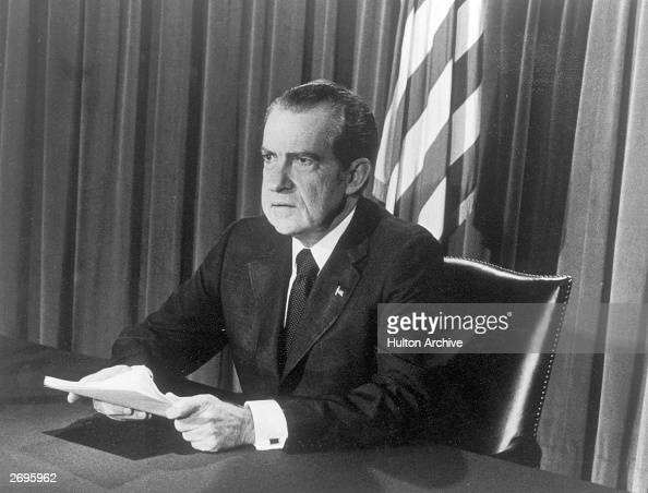 US President Richard M Nixon sits at a desk holding papers as he announces his resignation on television Washington DC