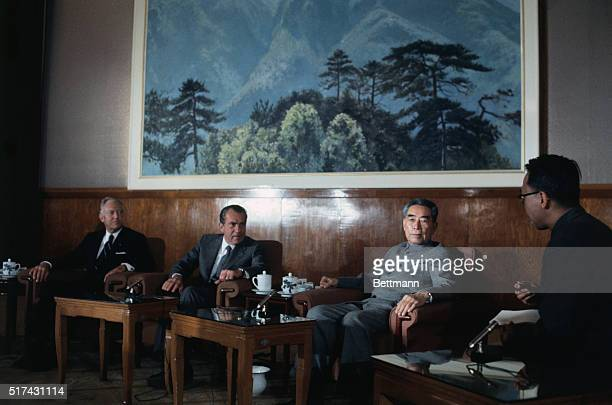 US President Richard Nixon and Communist Chinese Premier Chou EnLai sit with their advisors beneath a giant painting as they confer in the Great Hall...