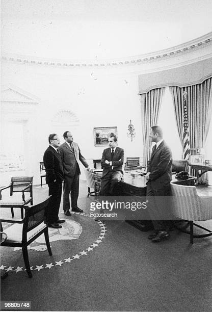 President Richard Nixon sits on desk while conferring with National Security Adviser Henry Kissinger General Counsel John Erlichman and White House...
