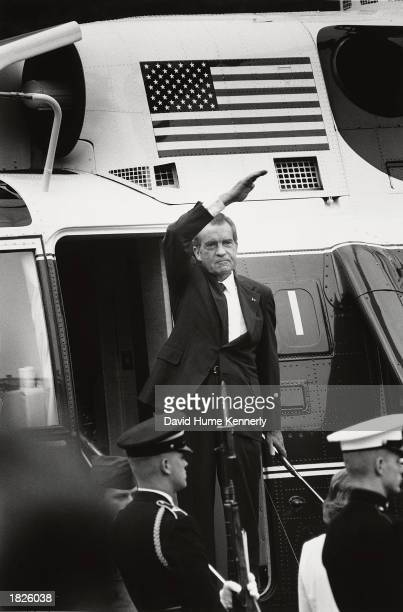 US President Richard Nixon stands on the steps of the presidential helicopter as he waves goodbye to the White House for the final time after...