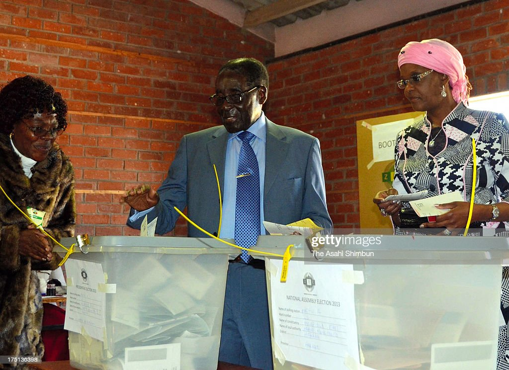 President <a gi-track='captionPersonalityLinkClicked' href=/galleries/search?phrase=Robert+Mugabe&family=editorial&specificpeople=214676 ng-click='$event.stopPropagation()'>Robert Mugabe</a> (C) casts a ballot at a vote center during the presidential election on July 31, 2013 in Harare, Zimbabwe. The result will be announced by August 5.