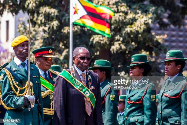 President Robert Mugabe inspects a guard of honour during the official opening of the 5th session of the 8th Parliament of Zimbabwe in Harare which...