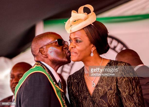 President Robert Mugabe kisses his wife and first lady Grace Mugabe during during the country's 37th Independence Day celebrations at the National...