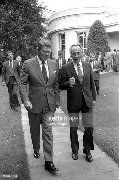 US President Ronald Reagan accompanies Israeli Prime Minister Shimon Peres to his car after their meeting in the White House October 9 1984 in...