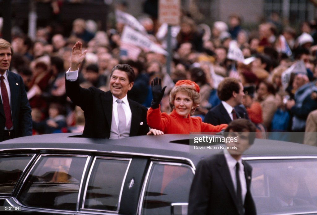 US President Ronald Reagan and wife Nancy wave to the crowd from the Presidential Limosine as they ride down Pennsylvania Avenue during the Inaugural...