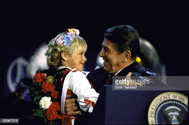 President Ronald Reagan holding child Jennifer Wjciechowski after she presented him flowers at a campaign speech