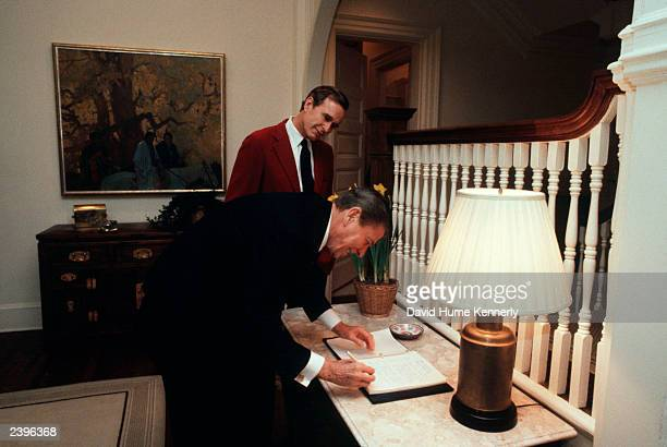 US President Ronald Reagan looks over paperwork as Vice President George Bush watches n the Vice President's residence February 23 1981 in Washington...