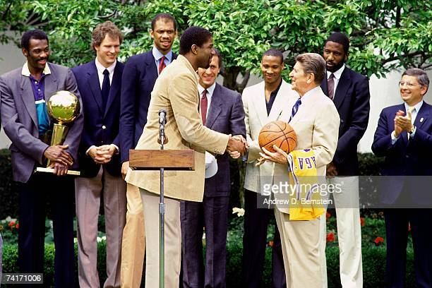 President Ronald Reagan shakes hand with Magic Johnson during the world champion Los Angeles Lakers visit to the White House in 1985 in Washington DC...