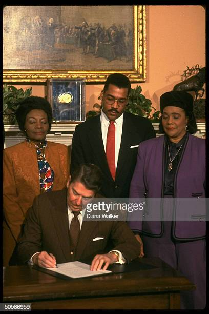 US President Ronald Reagan signing Martin Luther King Jr Day holiday proclamation with his Dr King's widow Coretta Scott King son Dexter sister...