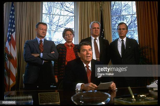 President Ronald Reagan sitting at desk in front of Vice President George Bush James Schlesinger Jeane Kirkpatrick and Zbigniew Brzezinski in the...