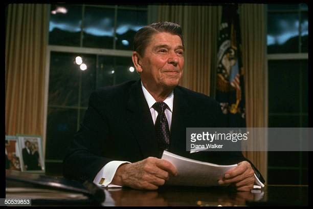 President Ronald Reagan sitting at desk in the Oval Office of the White House after adressing the nation re IranContra affair
