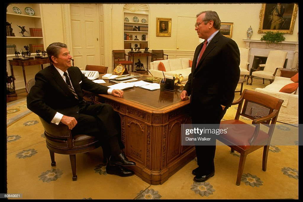 reagan oval office. president ronald reagan sitting at desk speaking to white house chief of staff howard baker oval office