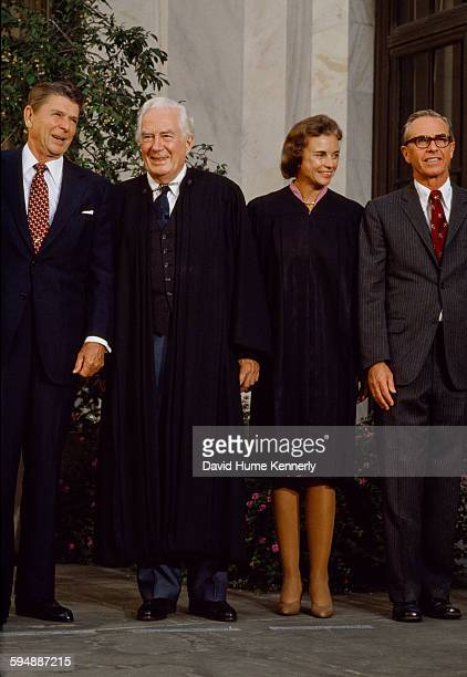 US President Ronald Reagan stands with US Supreme Court Chief Justice Warren Burger the newly appointed Associate Justice Sandra Day O'Connor and her...