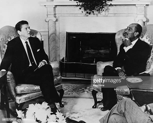 President Ronald Reagan talking to Egyptian President Anwar El Sadat in the Oval Office of the White House Washington DC 1981