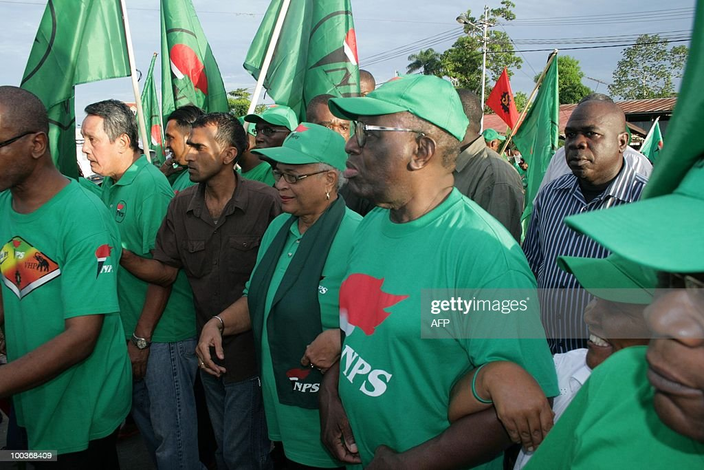 President Ronald Venetiaan (C) and his wife (L) surrounded by guards during a march on May 23, 2010 towards his enclosure meeting with thousands of supporters in the center of Paramaribo. The leader of coalition strongly believes in a huge victory together with his New Front partners. Now campaigning is allowed on May 24th, the day before the elections.