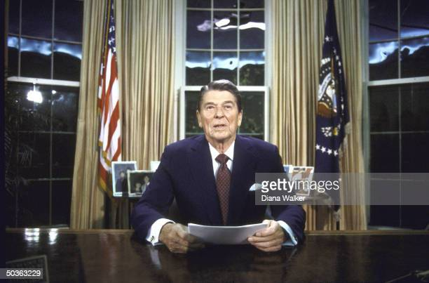 US President Ronald W Reagan seated at desk in Oval Office