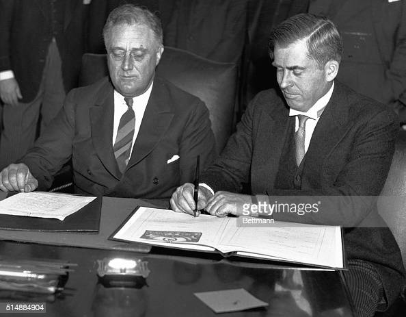 President Roosevelt and Secretary of Agriculture Henry Wallace sign a bill