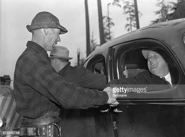 President Roosevelt is shown shaking hands with Fred Wilson lumberjack in the Olympic National Forest after Wilson provided a thrill for the...