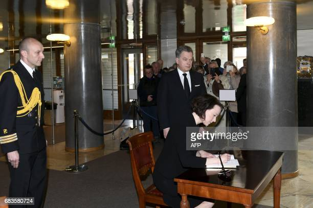 President Sauli Niinisto looks on as First lady Jenni Haukio signs the book of condolence for the late President of Finland Mauno Koivisto at the...
