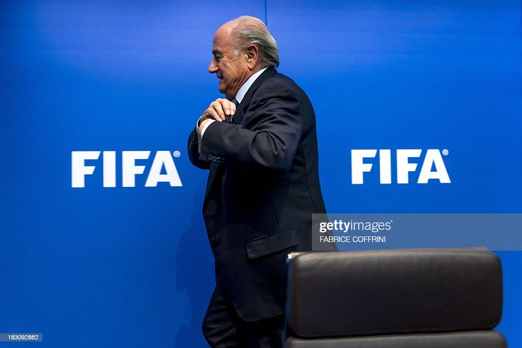 President Sepp Blatter leaves a press conference on October 4, 2013 at the FIFA headquarters in Zurich. FIFA said they could not get involved in labour issues in any country, amid calls for action after claims that dozens of migrant workers had died on construction projects linked to the 2022 World Cup in Qatar. Blatter, however said that the federation could not turn a blind eye to the reports, which also alleged that thousands of other workers endured conditions akin to 'modern-day slavery' in Qatar.