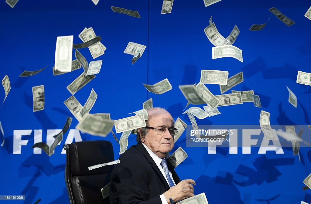 FIFA president Sepp Blatter looks on as fake dollar notes fly around him, thrown by a British comedian during a press conference at the FIFA world-body headquarter's on July 20, 2015 in Zurich. The 79-year-old Swiss official looked shaken as the notes thrown by Simon Brodkin, stagename Lee Nelson, fluttered around him in a conference hall at the FIFA headquarters. Brodkin was taken away in a Swiss police car after the stunt.