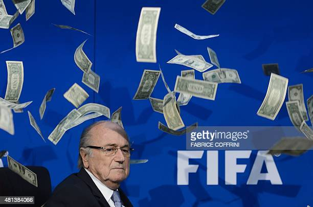 FIFA president Sepp Blatter looks on with fake dollars note flying around him thrown by a protester during a press conference at the football's world...