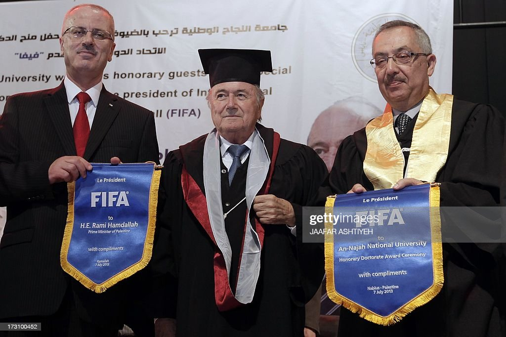 President Sepp Blatter (C) poses for a picture with Palestinian prime minister Rami Hamdallah (L) and the interim head of Al-Najah University (R) during an honorary doctorate ceremony in the University campus in Nablus on July 7, 2013. AFP PHOTO/JAAFAR ASHTIYEH