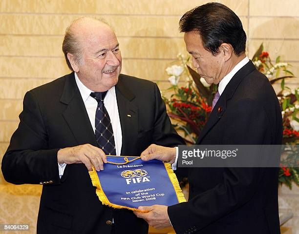 FIFA President Sepp Blatter presents a FIFA Club World Cup 2008 pennant to Japanese Prime Minister Taro Aso during his visit to the prime minister's...