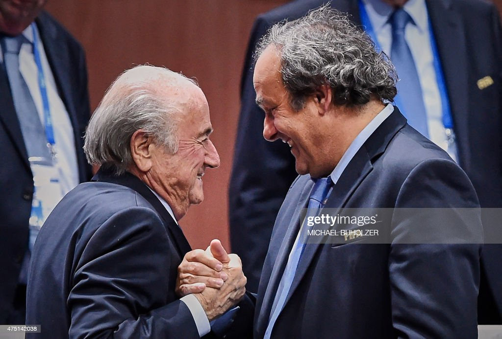 President <a gi-track='captionPersonalityLinkClicked' href=/galleries/search?phrase=Sepp+Blatter&family=editorial&specificpeople=209372 ng-click='$event.stopPropagation()'>Sepp Blatter</a> (Foreground-L) shakes hands with UEFA president <a gi-track='captionPersonalityLinkClicked' href=/galleries/search?phrase=Michel+Platini&family=editorial&specificpeople=206862 ng-click='$event.stopPropagation()'>Michel Platini</a> after being re-elected following a vote to decide on the FIFA presidency in Zurich on May 29, 2015. <a gi-track='captionPersonalityLinkClicked' href=/galleries/search?phrase=Sepp+Blatter&family=editorial&specificpeople=209372 ng-click='$event.stopPropagation()'>Sepp Blatter</a> won the FIFA presidency for a fifth time after his challenger Prince Ali bin al Hussein withdrew just before a scheduled second round. AFP PHOTO / MICHAEL BUHOLZER / AFP / MICHAEL BUHOLZER