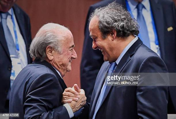 President Sepp Blatter shakes hands with UEFA president Michel Platini after being reelected following a vote to decide on the FIFA presidency in...